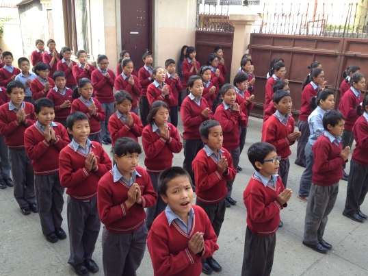 The students at the daily morning assembly before school reciting their prayers.